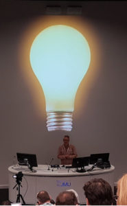 Neil Allison presenting a slide with a giant lightbulb on it