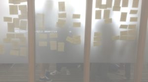 Post it notes and people seen through a glass wall