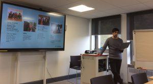Speaker stand beside slide while presenting
