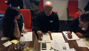 Person interacts with paper interface while two others watch and make notes