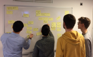 Students look at post it notes on a whiteboard