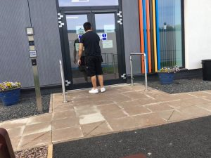 Person stands at closed doors reading notices pinned to them